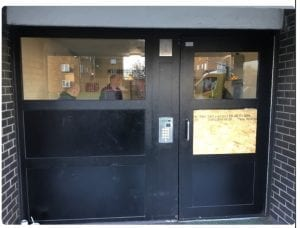 Non Warrior Communal Entrance Door with small window space and chipboard covering smashed glass panel