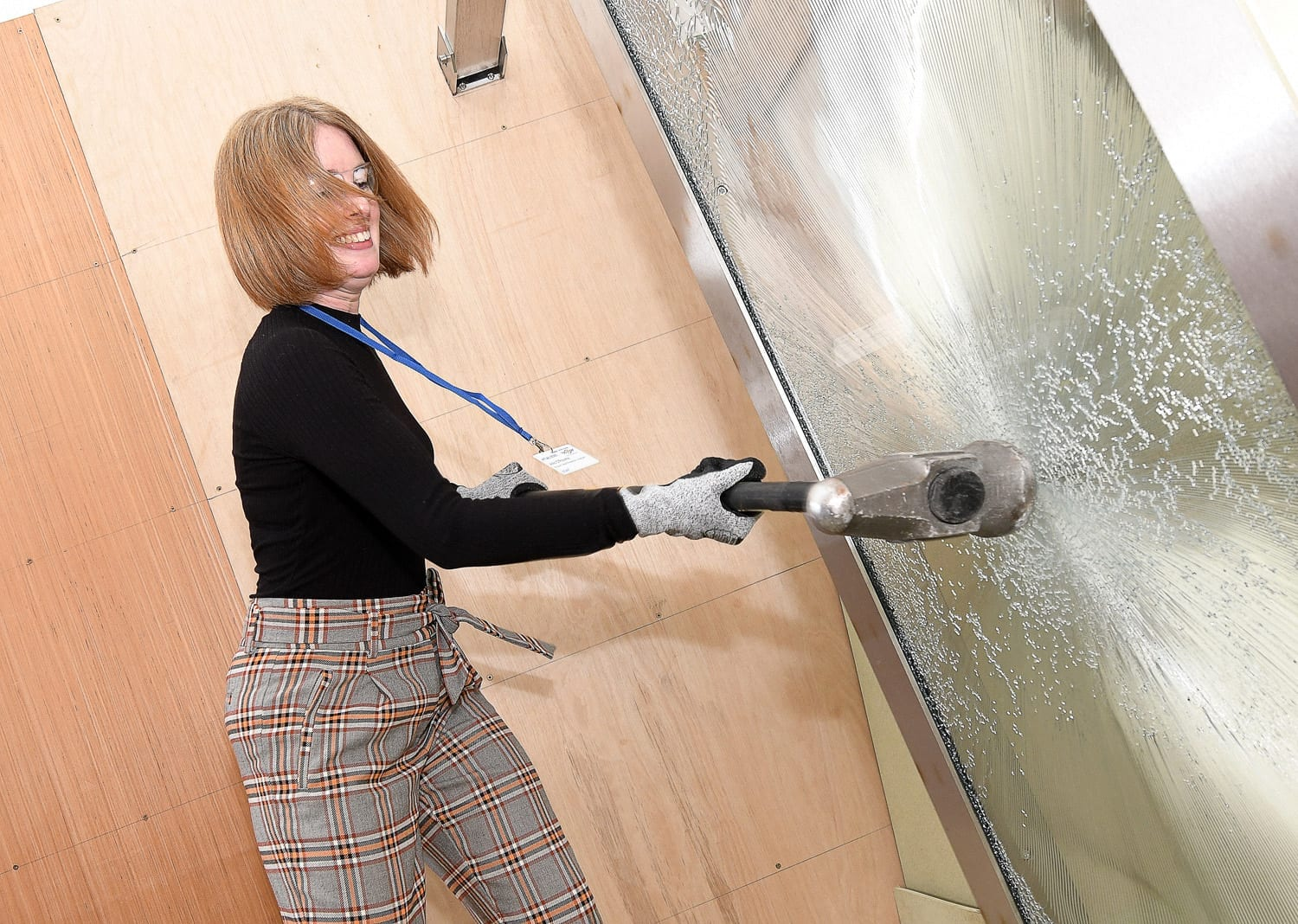Woman in gloves and goggles hitting glass door with a sledge hammer