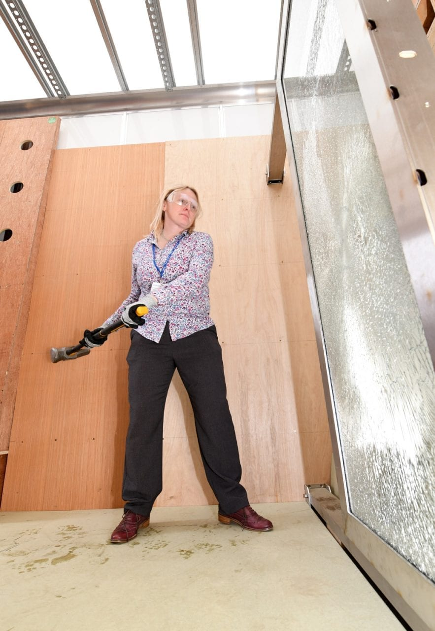 full body shot of woman about to hit a glass door with a sledgehammer