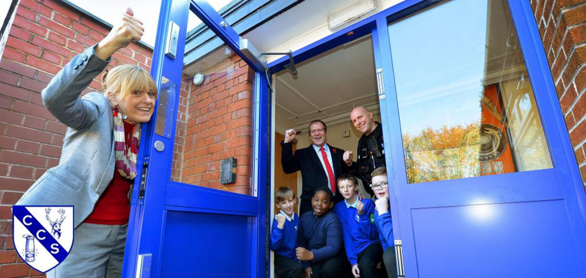 Brett Barratt, a security guard, 4 students and the head teacher of Chasetown Community school celebrating next to their Warrior 2gg Swing Door & Screen