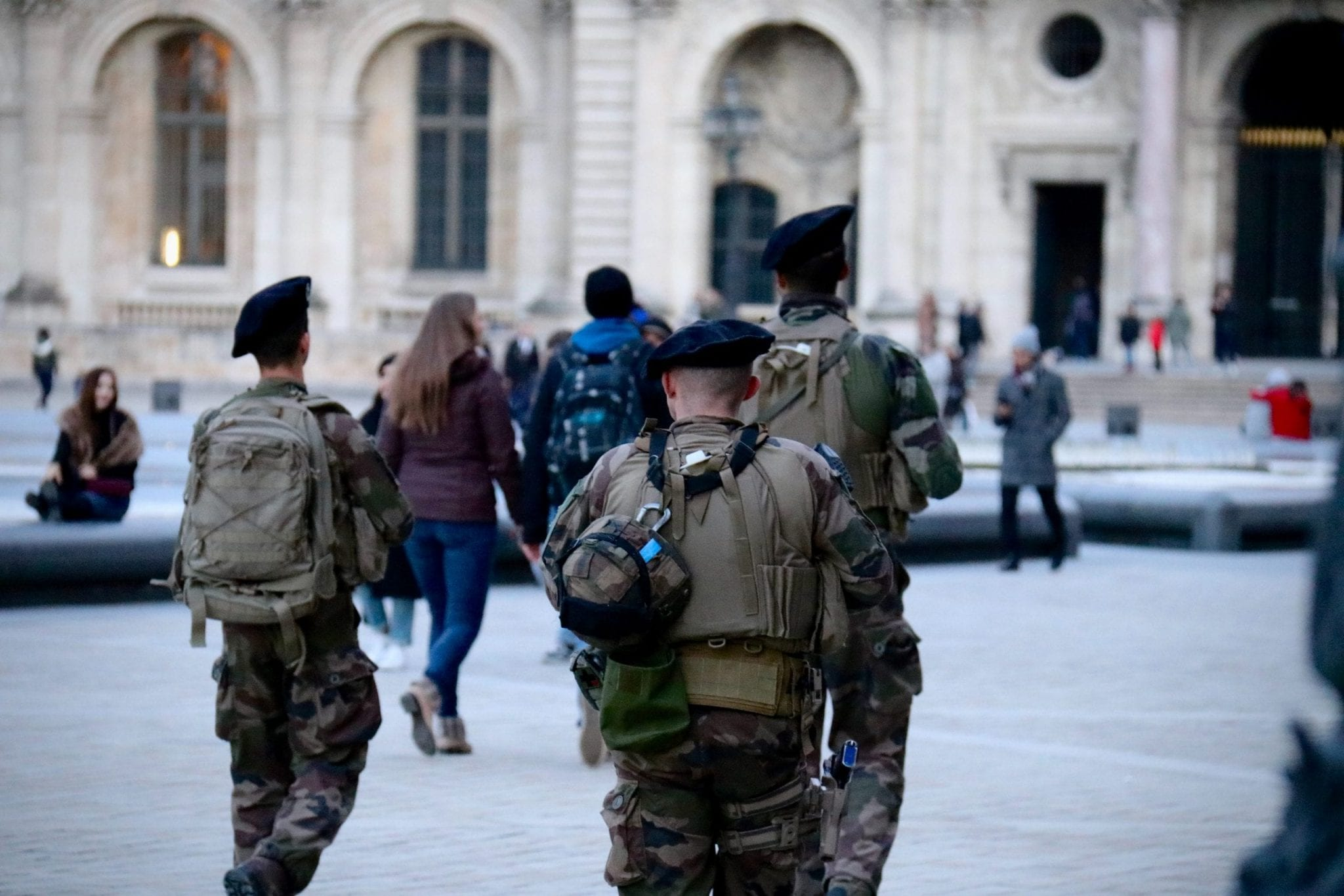 men in military uniforms walking towards a large building.
