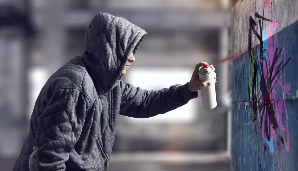 Man in a hoodie spray painting on a wall