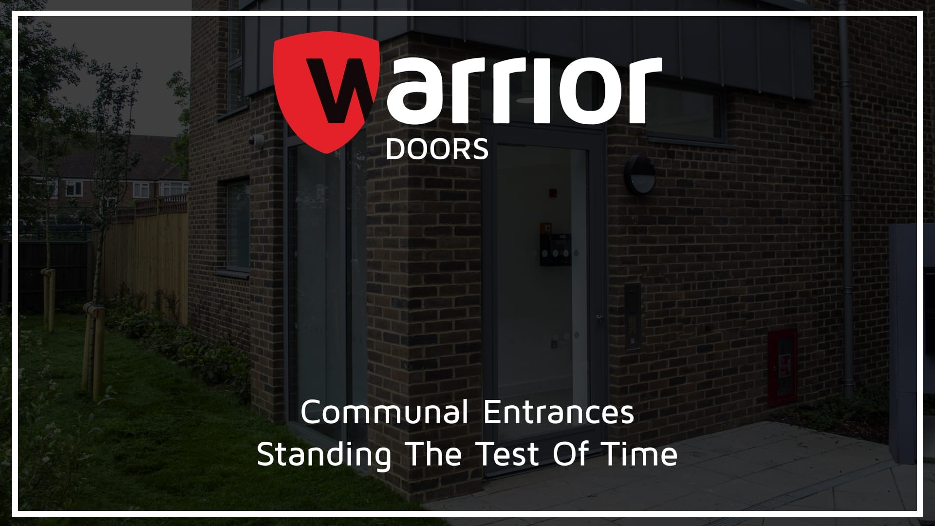 """Warrior Fully Glazed Communal Entrance Door & Screen on a Communal Residential Building with Warrior Doors Logo and tect reading """"CommunalEntrances Standing The Test Of TIme"""""""