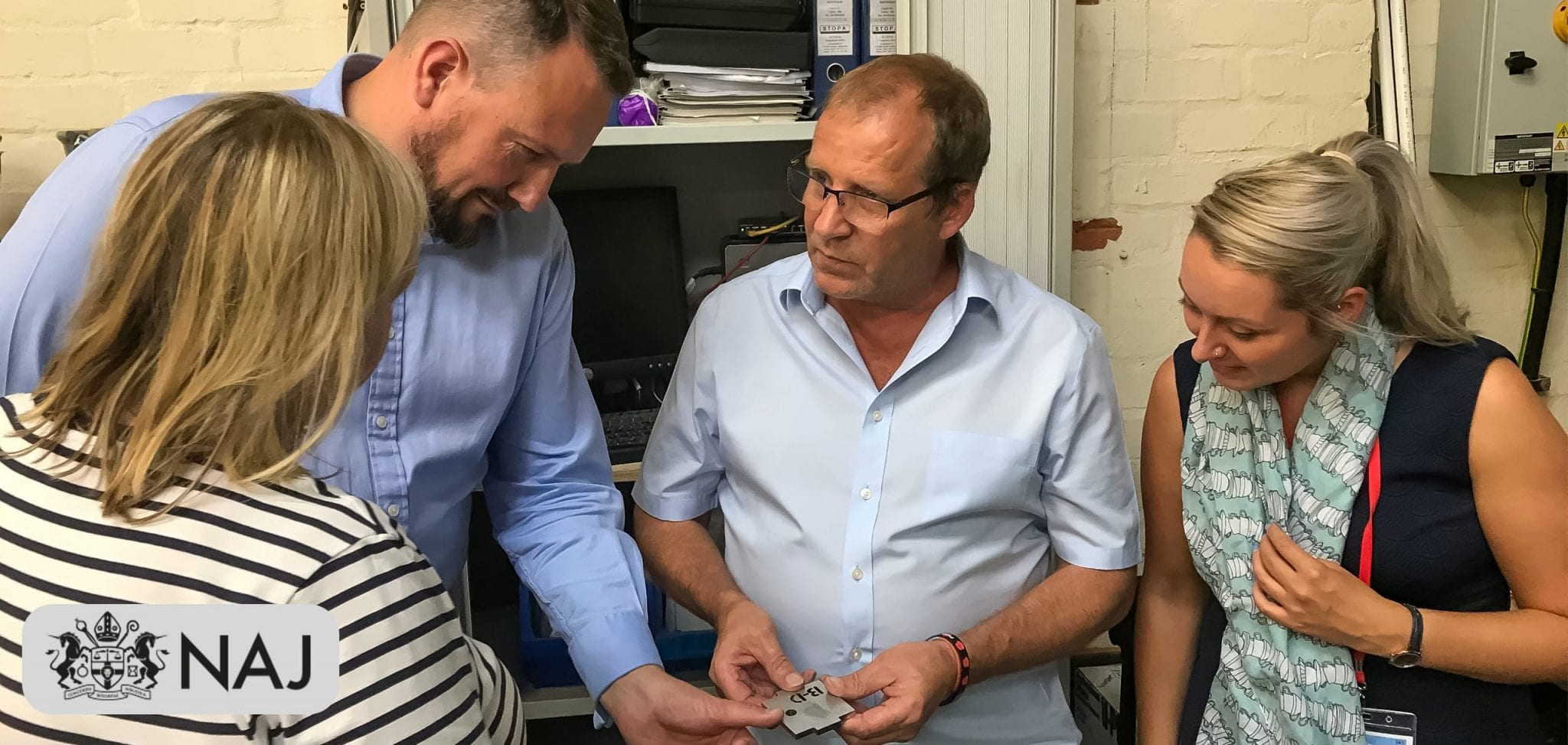 Managing Director Brett Barratt and three members of the National Association of Jewellers looking at a piece of cut stainless-steel. NAJ logo in the bottom left corner.