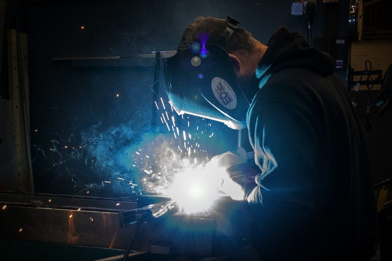 Man in welding mask and gloves welding stainless-steel. Lots of sparks.