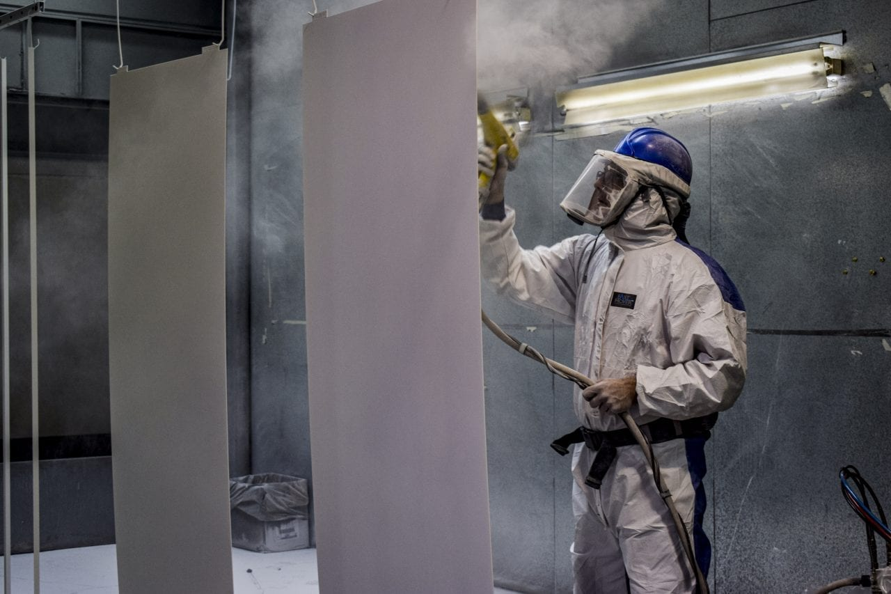 Man in protective suit powder coating stainless-steel sheets.