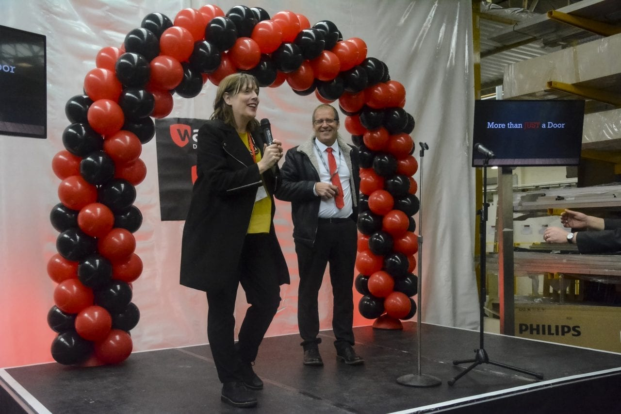 Managing Director Brett Barratt and local MP Jess Phillips holding microphones on stage at Warrior Doors' 20th anniversary party. Red and black balloon arch and tvs behind them.