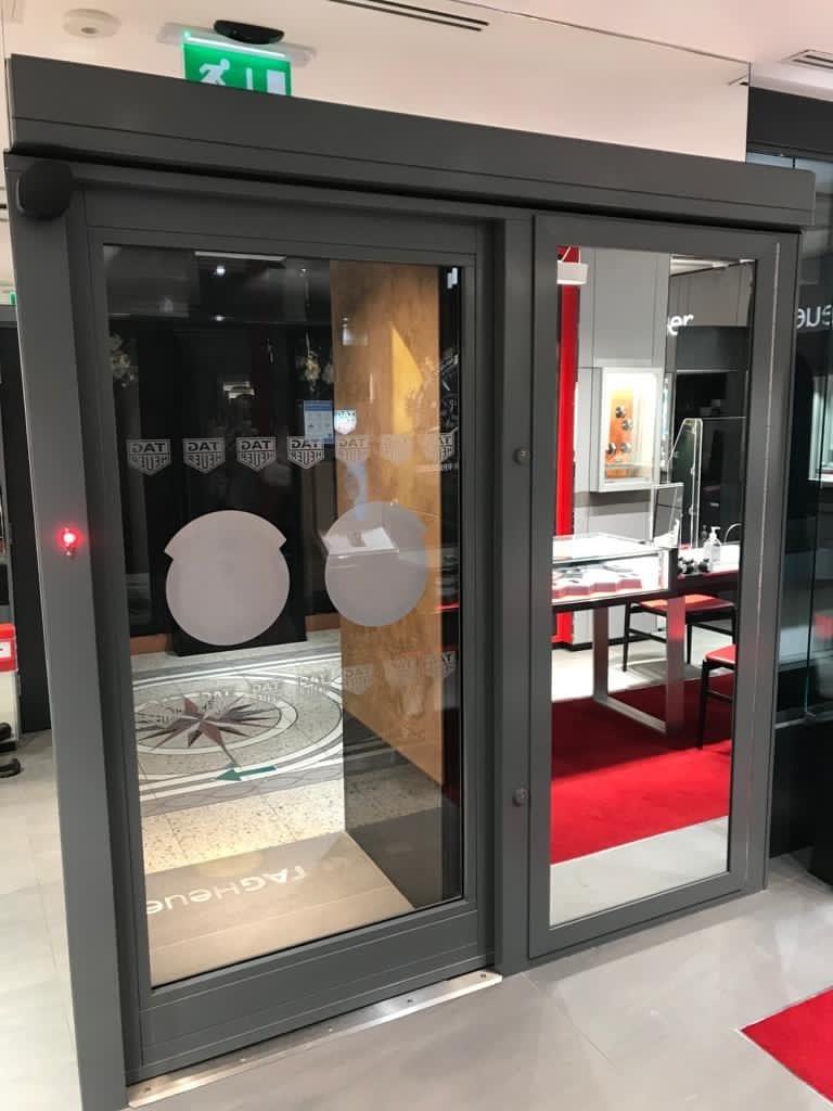 Grey Warrior Sliding Door inside a watch showroom.
