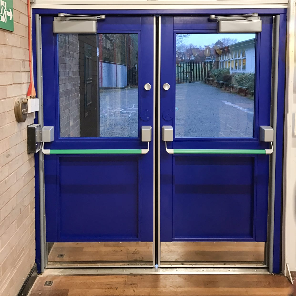 Blue Warrior Double School Security Door taken from the inside. Glass panels revealing the school playground outside. Green push to exit bars for easy visibility.