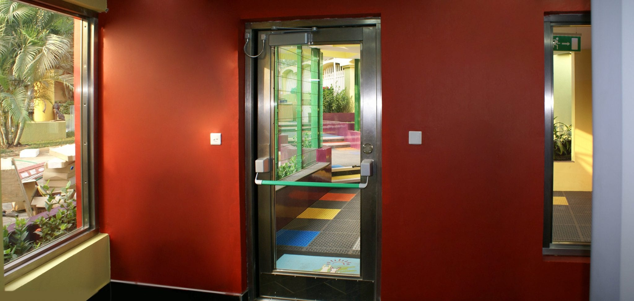 Fully glazed stainless-steel Warrior Fire Escape door with a green push to exit bar for easy visibility. Inside a school in Nigeria.