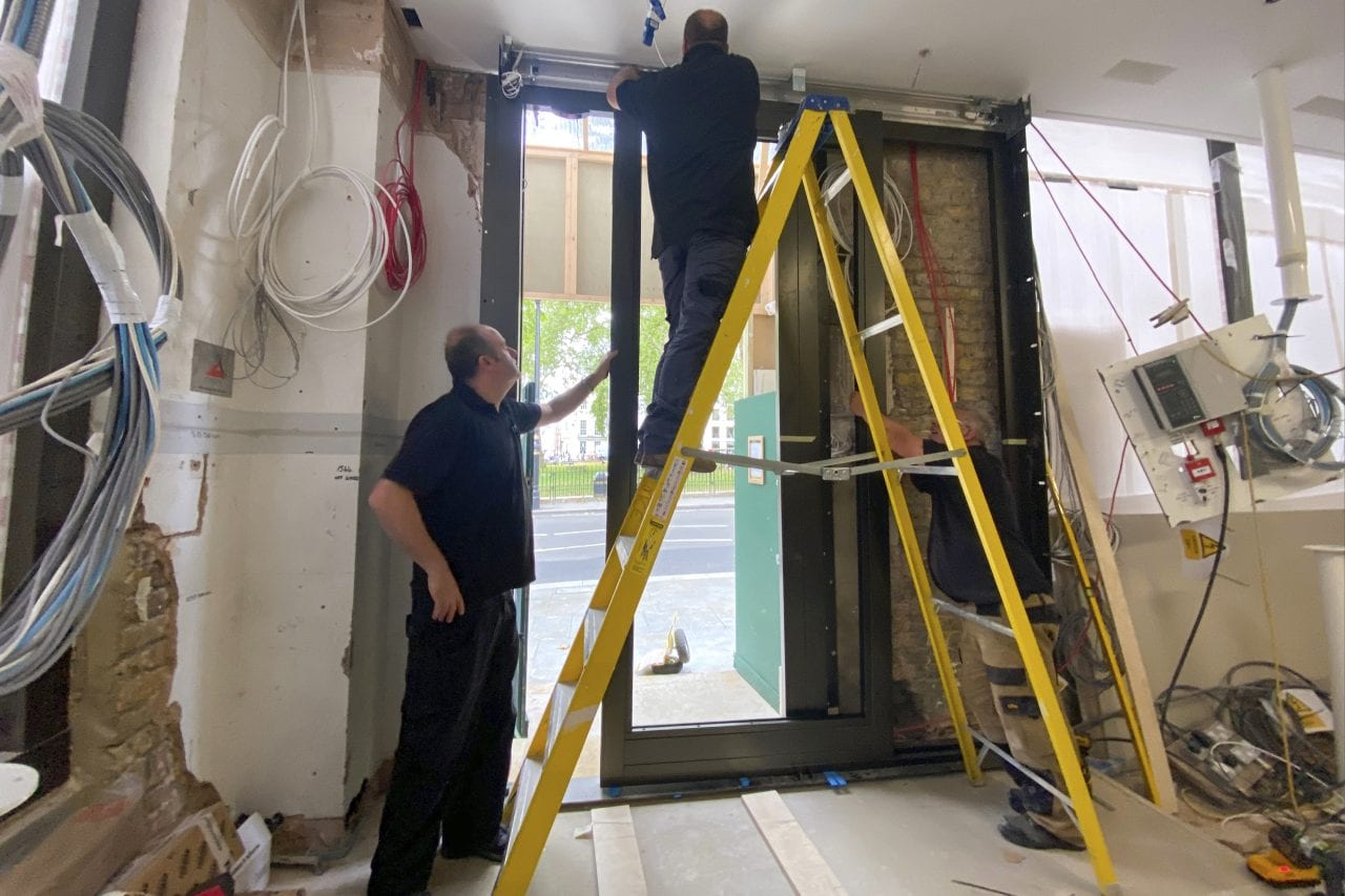 Three Warrior Doors installers. Two are supporting a large yellow ladder while the third stands on the ladder to work on the elctricals at the top of the door that they are installing. Set inside a jewellery store that is being built.