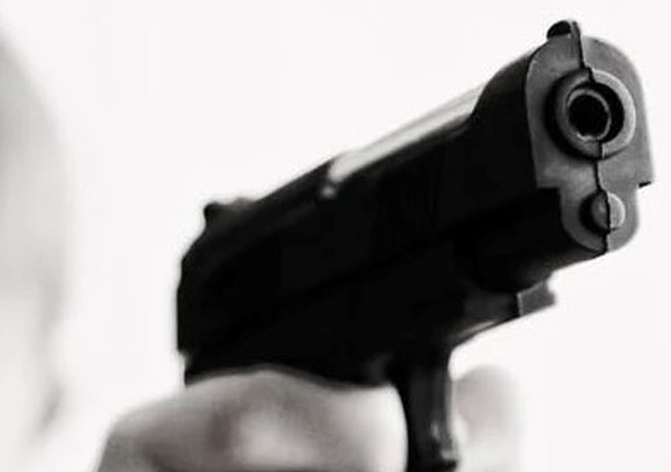 close up of a hand pointing a gun at the camera.