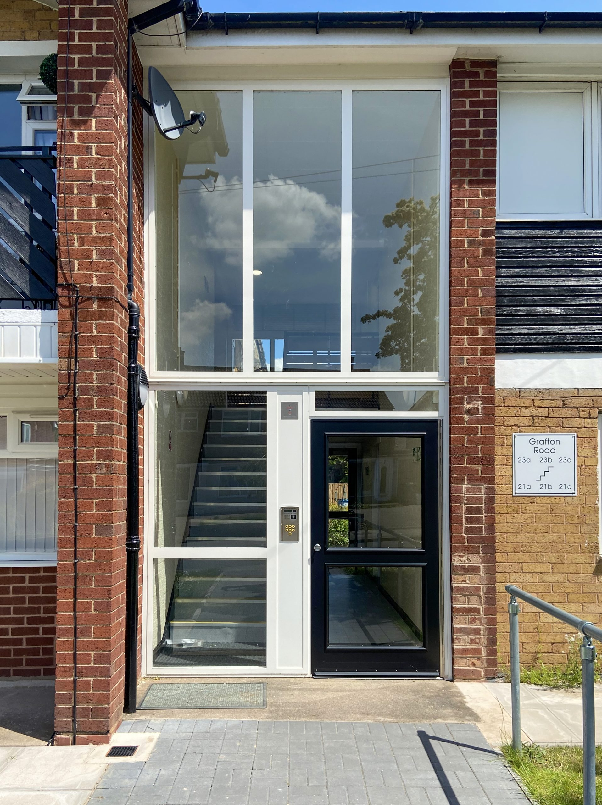 black door with a white frame and screens on a communal housing block