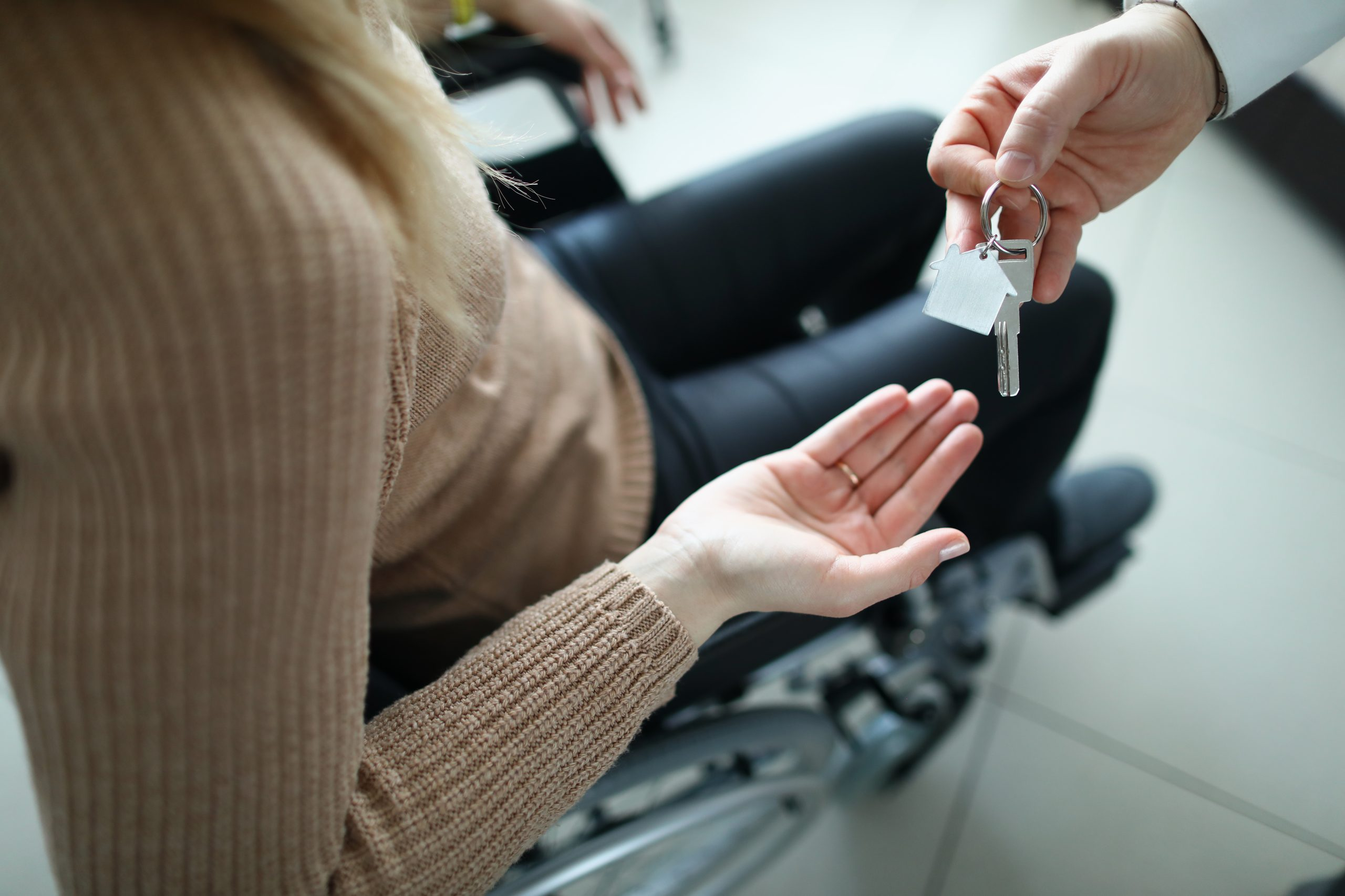 woman in wheelchair being handed house keys