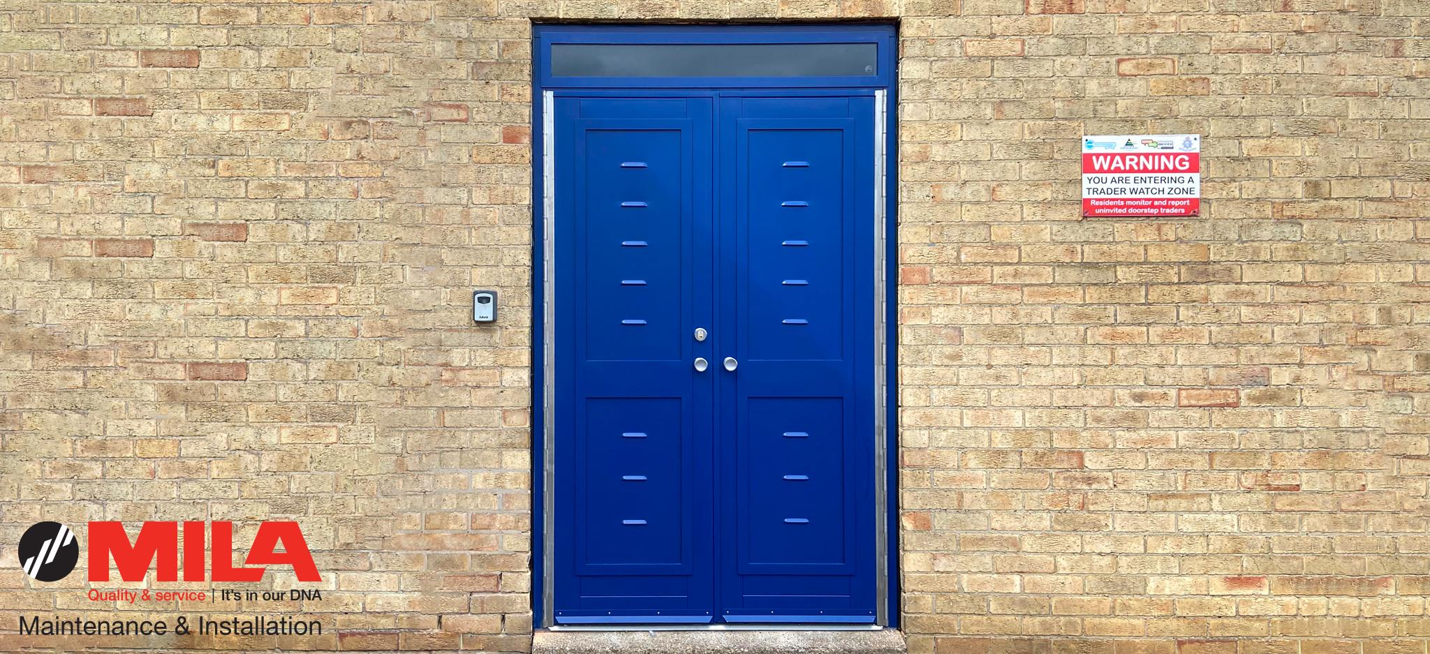 blue bin store door on a brick wall with Mila Maintenance & Installations Logo