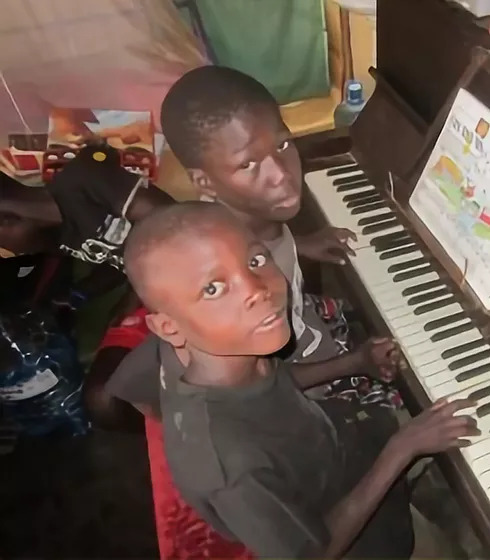 2 children using a piano sent by Africa Equip