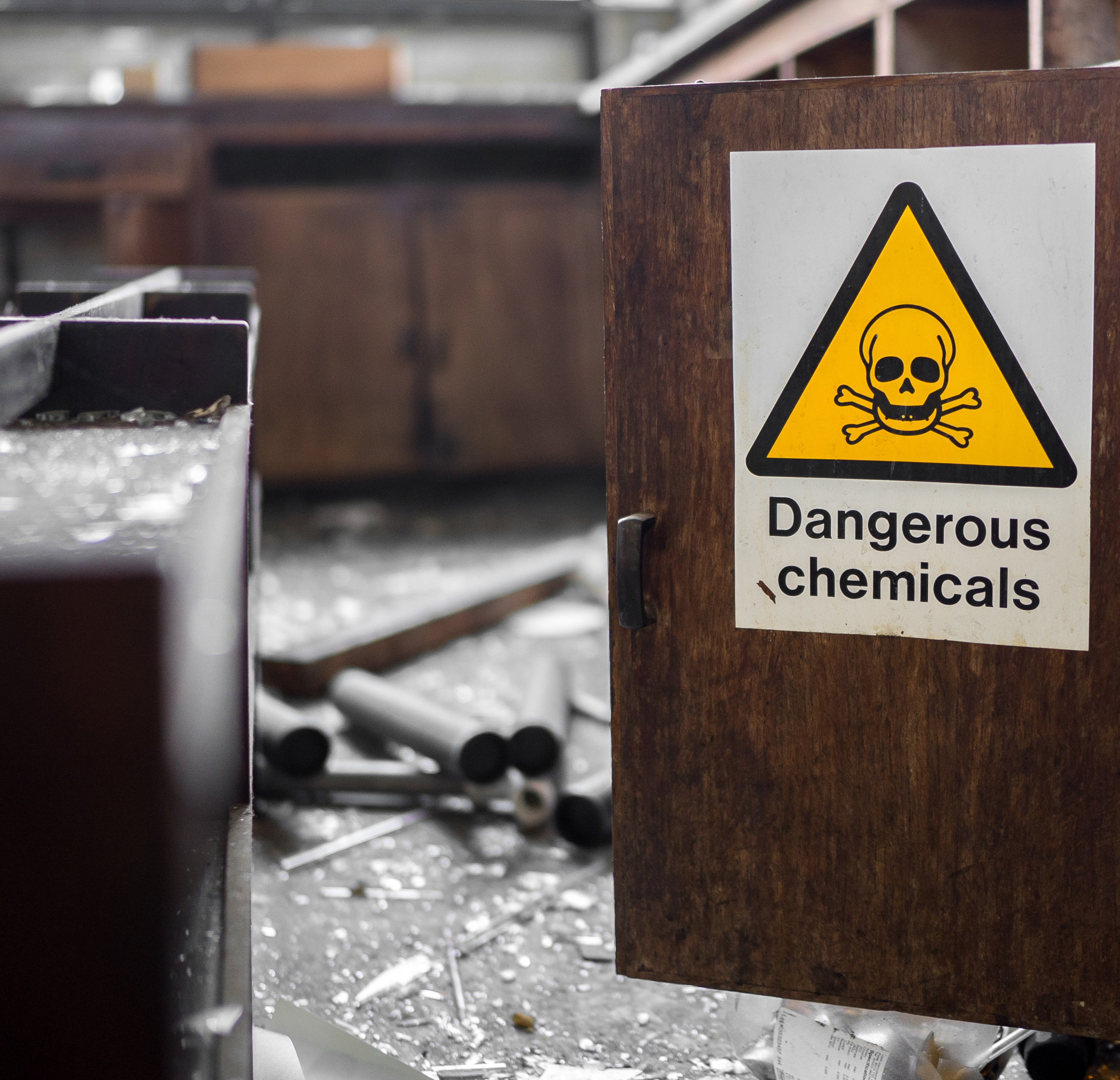 Dangerous Chemicals Sign on a cupboard with smashed glass around from break in